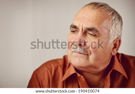 Thoughtful senior man with a moustache sitting reminiscing staring down at the ground with a serious contemplative expression - stock photo