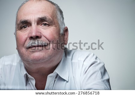 Thoughtful senior man with a moustache sitting reminiscing staring the with a serious contemplative expression - stock photo