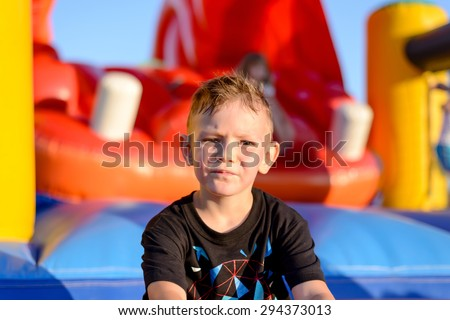 Thoughtful serious little boy in a kids playground sitting in the evening sunshine in front of a colorful jumping castle