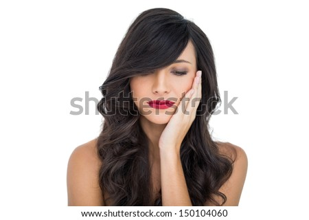 Thoughtful sexy brunette with red lips touching her cheek on white background - stock photo