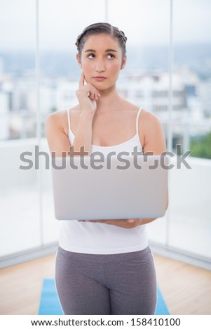 Thoughtful sporty brunette using her laptop in bright fitness studio - stock photo