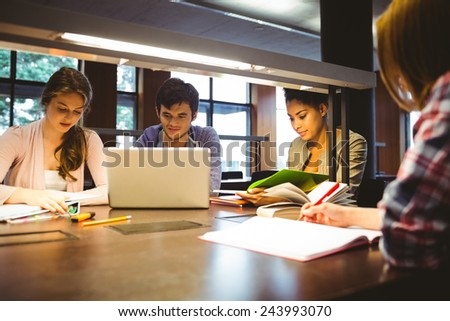 Thoughtful students working together at desk using laptop in library - stock photo