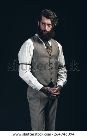 Thoughtful stylish bearded businessman standing clasping his hands in front of him looking to the side with a watchful expression, hands have tattoos, over a dark background - stock photo