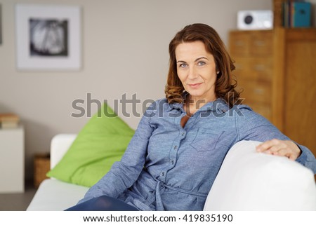 Thoughtful stylish middle-aged woman in smart leisurewear relaxing on a sofa at home looking at the camera with a pensive expression - stock photo