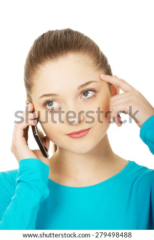 Thoughtful teen woman talking on the phone. - stock photo
