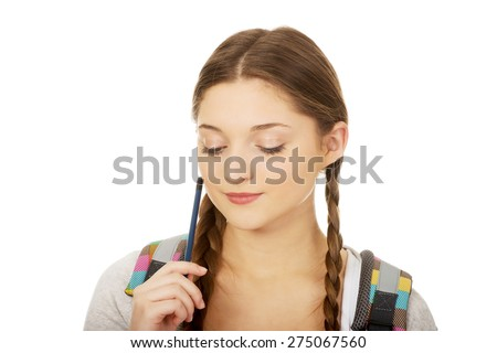 Thoughtful teenage girl with schoolbag and pen. - stock photo
