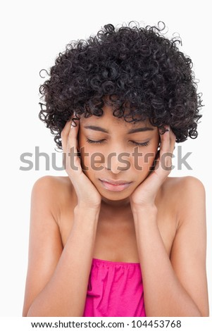 Thoughtful teenager seriously placing her hands on her temples - stock photo