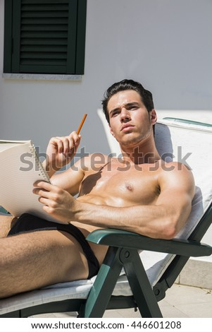 Thoughtful topless young man in deckchair with pencil and notebook