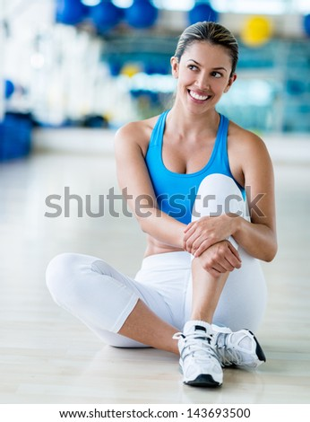 Thoughtful woman at the gym sitting on the floor - stock photo