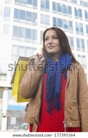 Thoughtful woman carrying shopping bags in winter - stock photo
