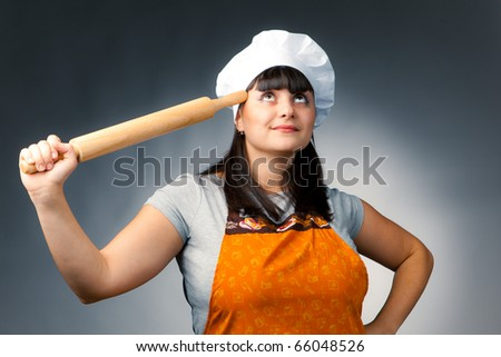 thoughtful woman cook holding a rolling pin - stock photo