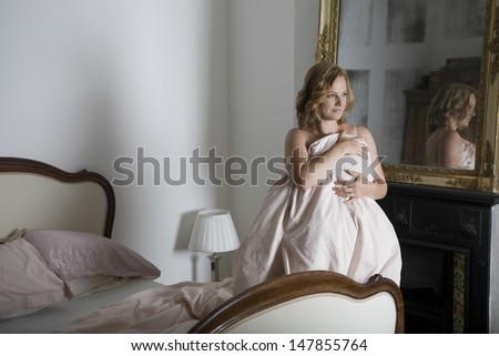 Thoughtful woman covering herself with quilt besides bed at home - stock photo
