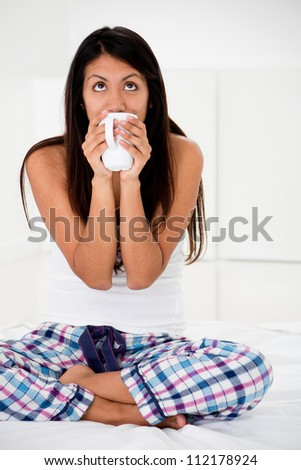 Thoughtful woman in bed while drinking coffee - stock photo