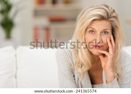 Thoughtful woman looking at the camera as she relaxes at home with her chin on her hand and a pensive expression - stock photo