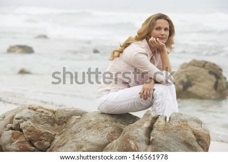 Thoughtful woman looking away while sitting on rock at beach