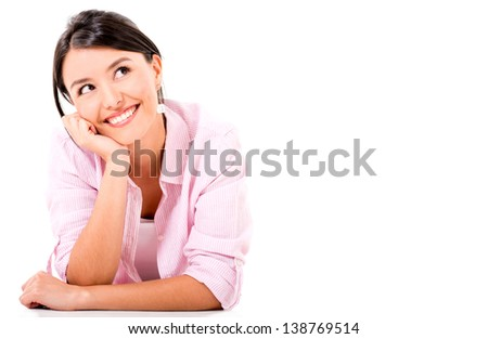 Thoughtful woman lying on the floor smiling - isolated over white - stock photo
