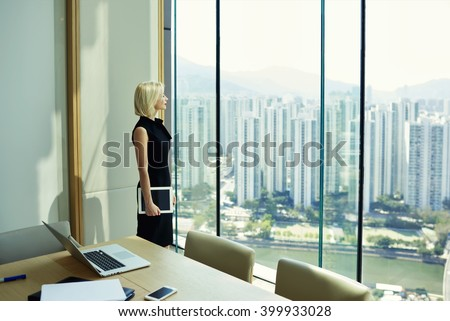 Thoughtful woman professional banker with touch pad in hand is watching in big office window with cityscape view,while is standing near meeting table with open laptop computer,phone and paper document