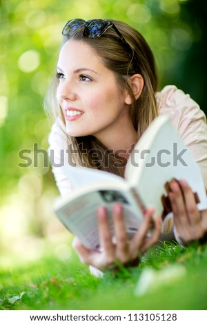 Thoughtful woman reading a book outdoors and smiling - stock photo