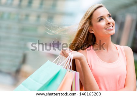 Thoughtful woman shopping holding bags at the mall - stock photo