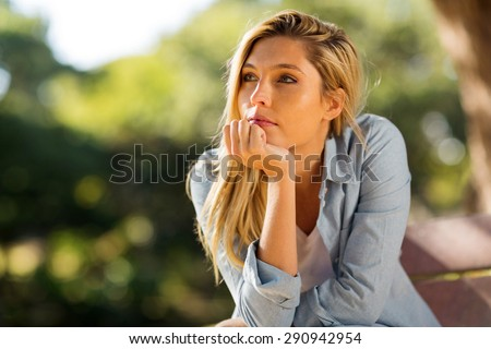 thoughtful woman sitting alone outdoors - stock photo