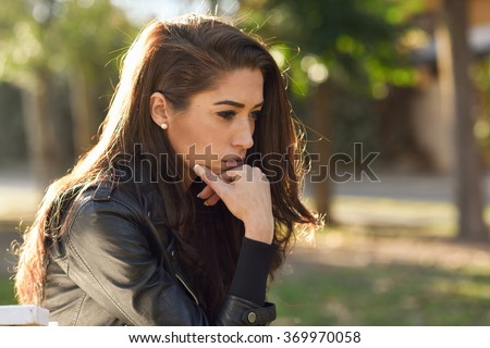 Thoughtful woman sitting alone outdoors. Girl worried in an urban park - stock photo