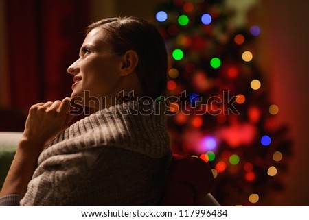 Thoughtful woman sitting chair in front of Christmas tree - stock photo
