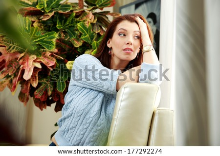 Thoughtful woman sitting on the sofa and looking in window at home