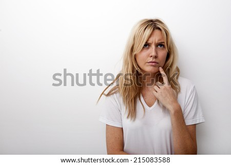 Thoughtful woman standing against white background - stock photo