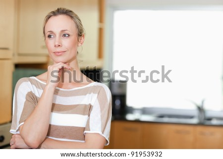 Thoughtful woman standing in the kitchen - stock photo