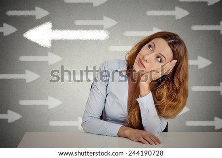 Thoughtful woman taking a chance going against flow. Thoughtful businesswoman sitting at table isolated on grey wall office background. Counterbalance concept. Face expression, emotion, intuition  - stock photo