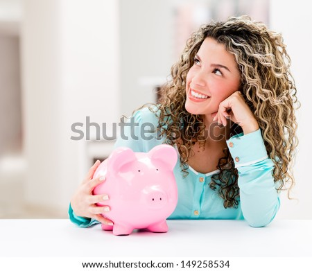 Thoughtful woman with a piggybank looking very happy  - stock photo
