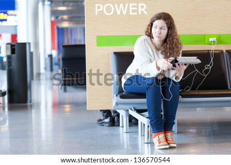 Thoughtful woman with electronic devices near place to charge your phone - stock photo