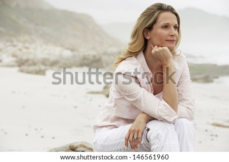 Thoughtful woman with hand on chin looking away while sitting on rock at beach - stock photo