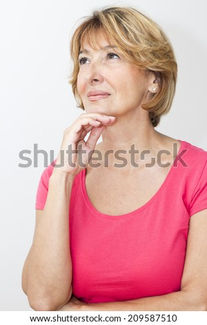 Thoughtful woman with hand on chin over. - stock photo