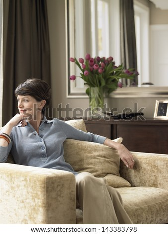 Thoughtful woman with hand on chin sitting on armchair at home