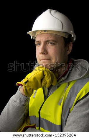 thoughtful workman in protective clothing, on black background