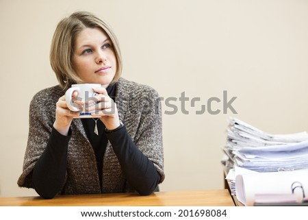 Thoughtful yong woman drinking coffee, blueprints at the table - stock photo