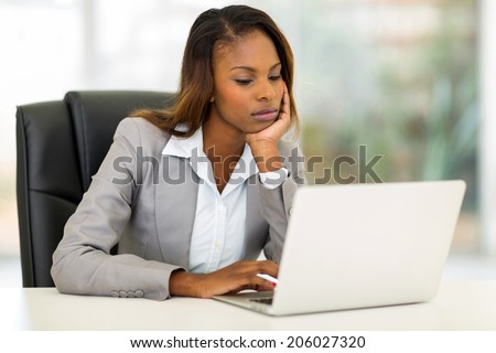 thoughtful young african businesswoman looking at the laptop screen - stock photo