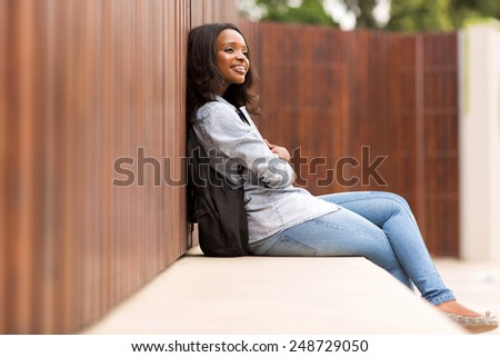 thoughtful young african college girl sitting outdoors - stock photo