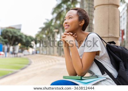 thoughtful young african college girl sitting outdoors on campus - stock photo