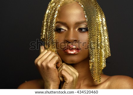 Thoughtful young black woman looking away with golden accessories, make-up holding hands near face - stock photo