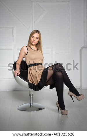 Thoughtful young blonde posing in sexy beige dress and stockings - stock photo