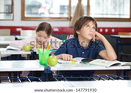 Thoughtful young boy looking up with girl in background at classroom - stock photo