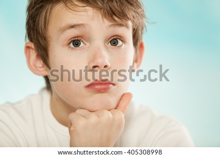 Thoughtful young boy watching intently with his chin resting on his hand and a wide-eyed expression, cropped head and shoulders - stock photo