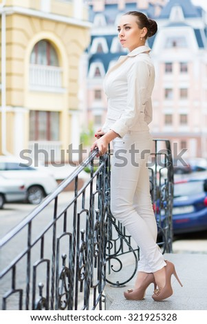 Thoughtful young brunette in white pants and jacket posing outdoors - stock photo