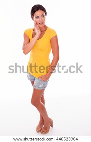 Thoughtful young brunette touching her cheek and looking away thoughtfully while wearing a yellow t-shirt and short jeans on white background