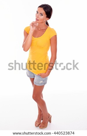 Thoughtful young brunette touching her chin and looking at camera thoughtfully while wearing a yellow t-shirt and short jeans on white background