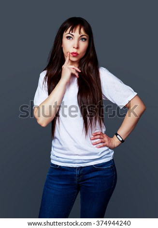 thoughtful young brunette woman against grey studio background - stock photo