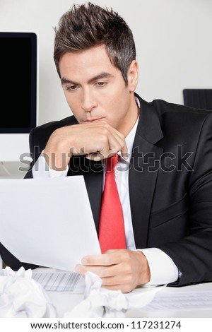 Thoughtful young businessman reading document at desk in office - stock photo