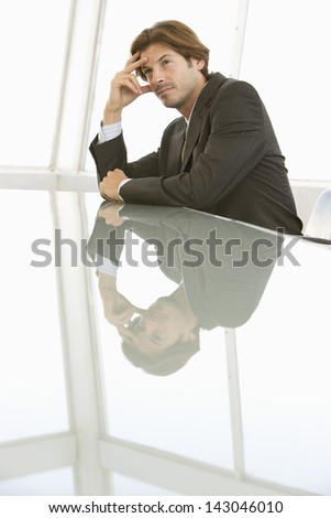 Thoughtful young businessman sitting at conference table - stock photo